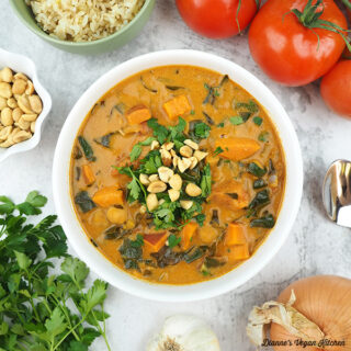 one bowl of stew with tomatoes, rice, onion, garlic, peanuts, and parsley square