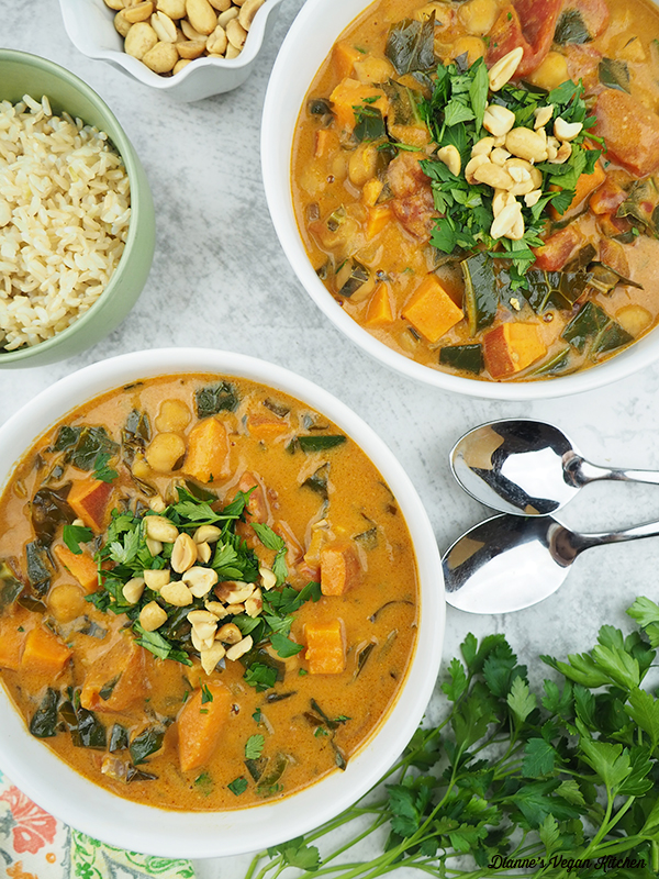 two bowls of Chickpea Peanut Stew with rice, peanuts, and spoons