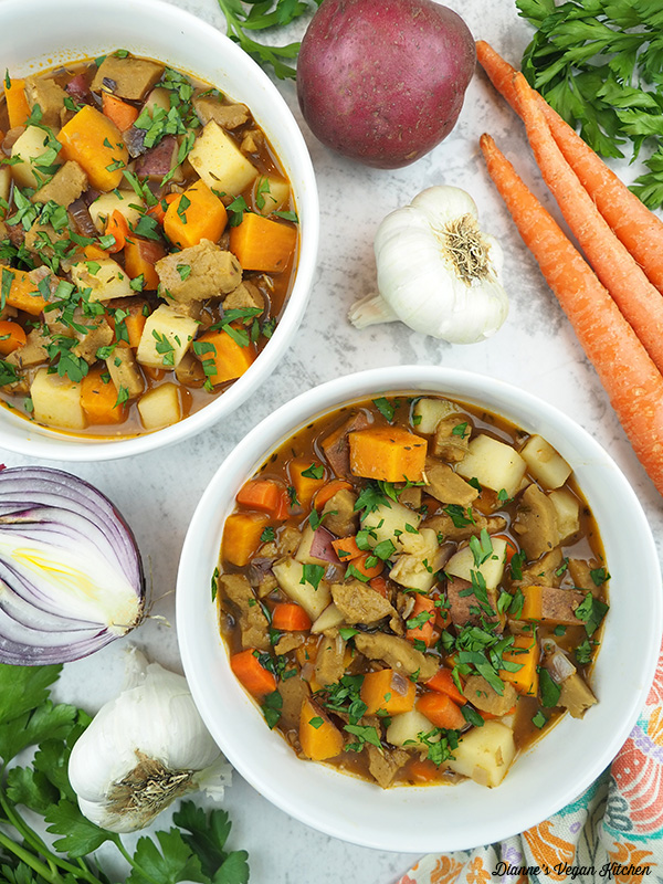 Two bowls of Seitan Stew overhead with carrots, onion, garlic, potatoes, and parsley