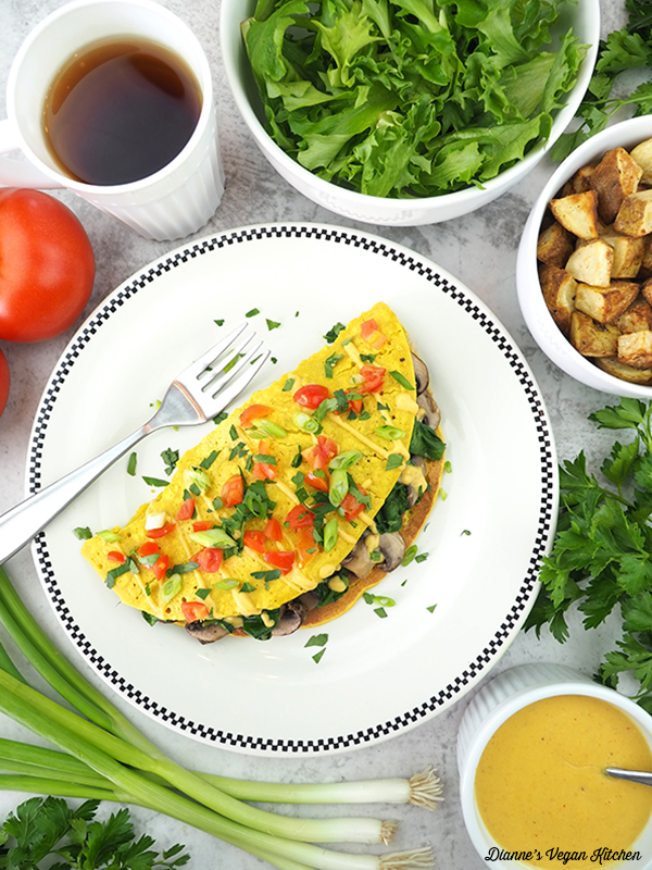 Vegan Spinach Mushroom Omelet with salad, potatoes, cheese sauce, and tea