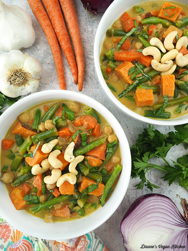 two bowls of curry with carrots, garlic, and onion