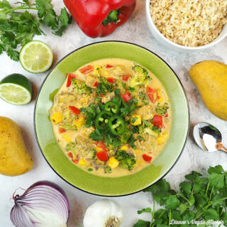 bowl of curry with vegetables, mango, and rice, square
