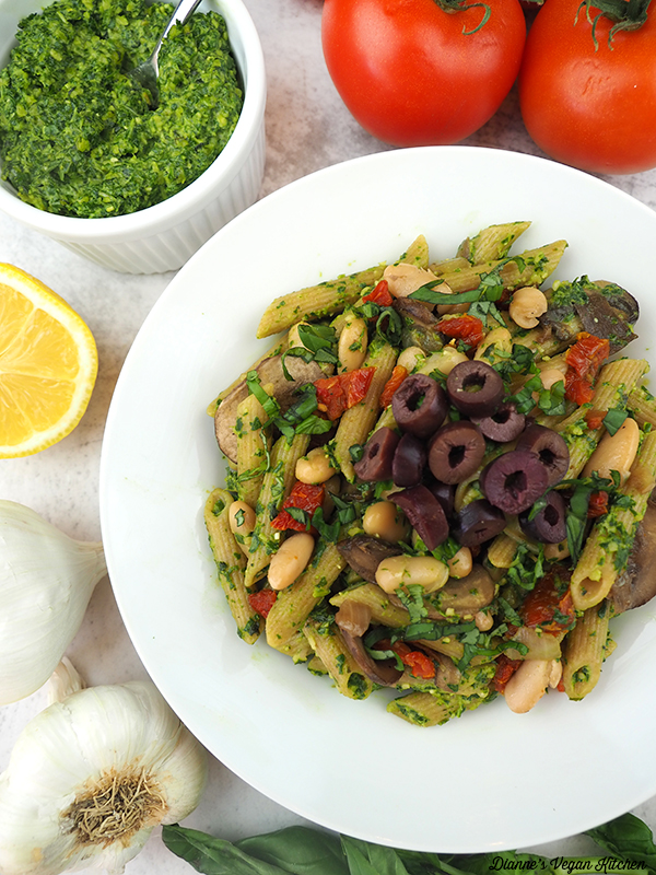 one bowl of pasta overhead with pesto, tomatoes, and garlic