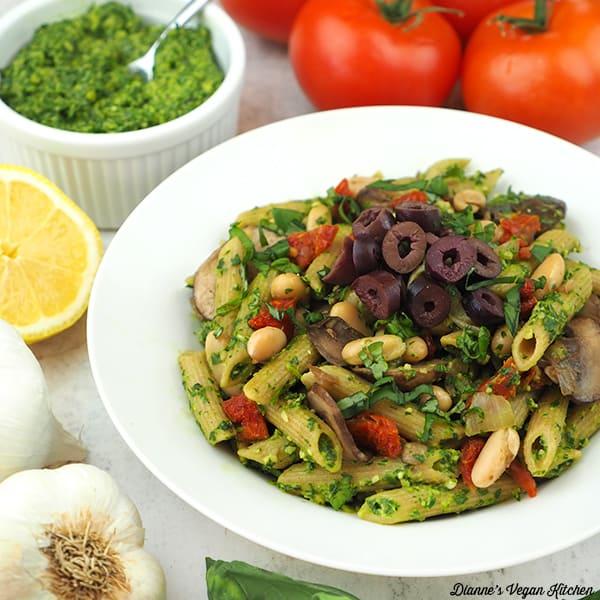 vegan pesto pasta with tomatoes, garlic, and pesto, square.