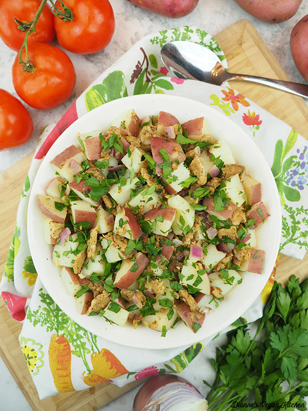 potato salad on cutting board with spoon, potatoes, tomatoes, onion, and parsley