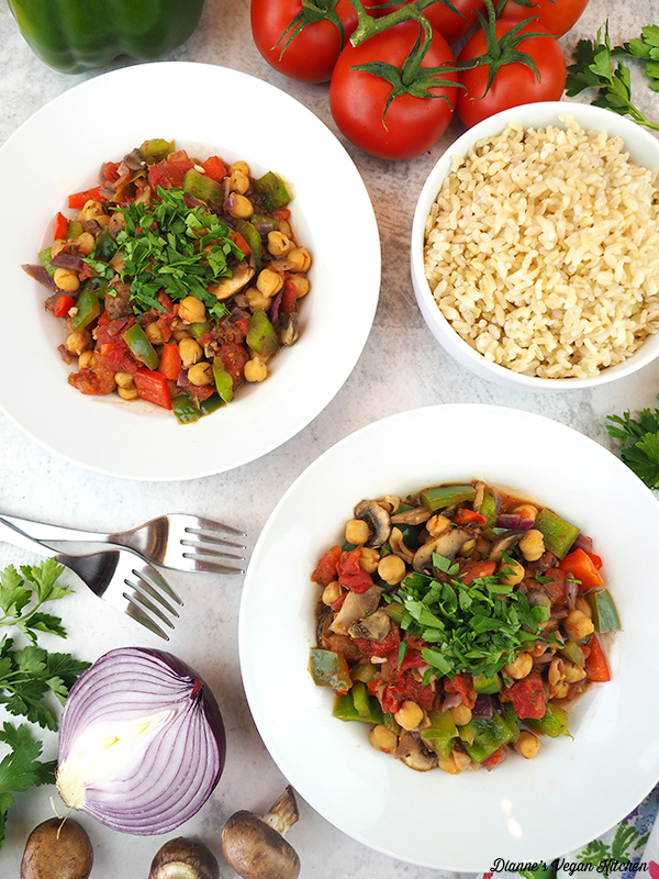 two bowls of vegan chickpea cacciatore with bowl of rice and forks