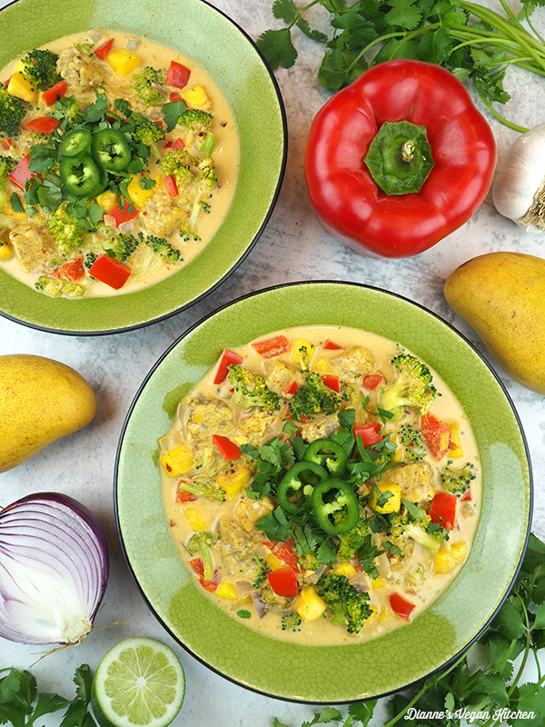 two bowls of curry overhead with peppers, mangos, onion, and lime