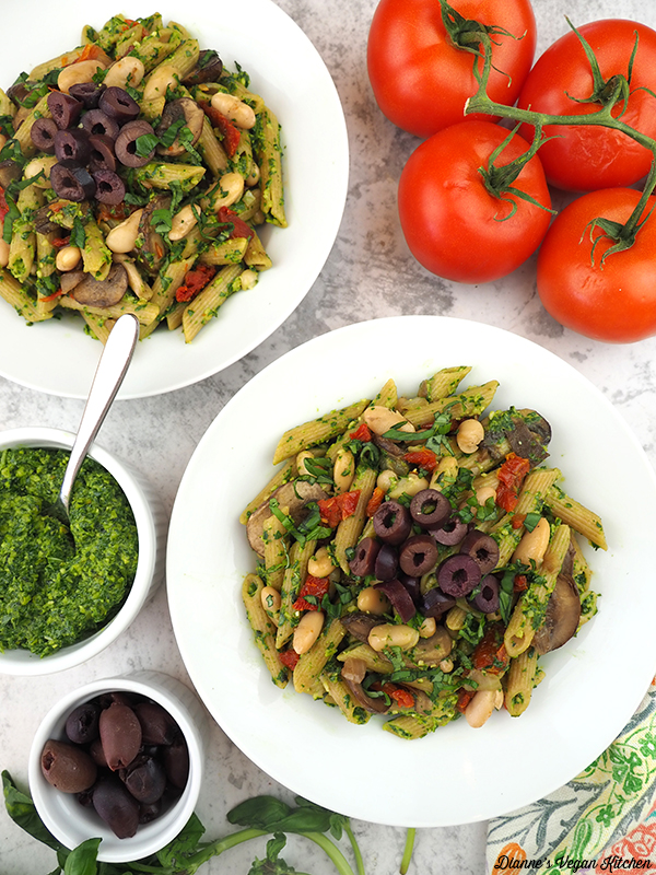 two bowls of pasta overhead with pesto and tomatoes