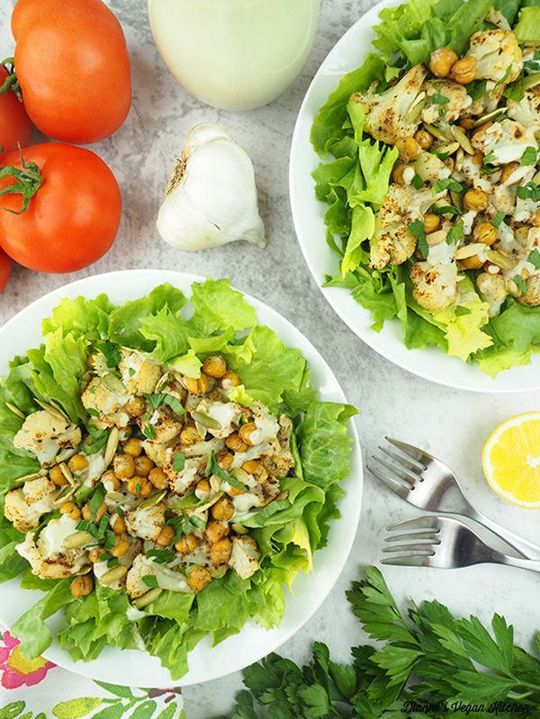 two bowls of Roasted Cauliflower Salad with tomatoes, lemon, garlic, and dressing