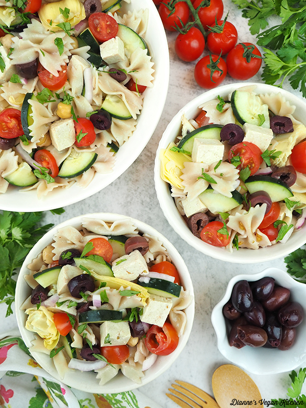 two small bowls of pasta salad with serving bowl