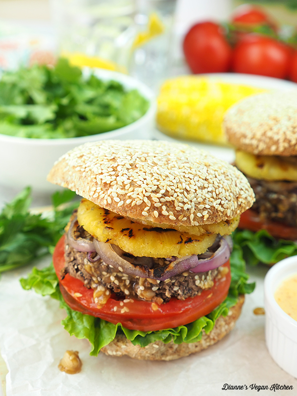 two burgers with corn on the cob and salad