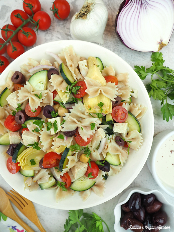 close up of greek pasta salad with tomatoes, onions, olives, and tahini