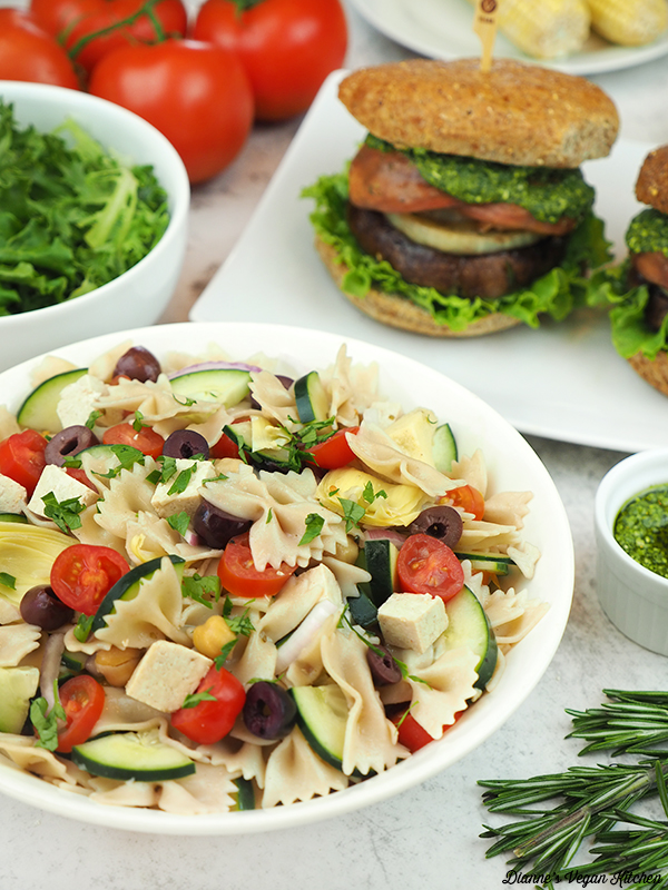 bowl of pasta salad with sandwiches in the background