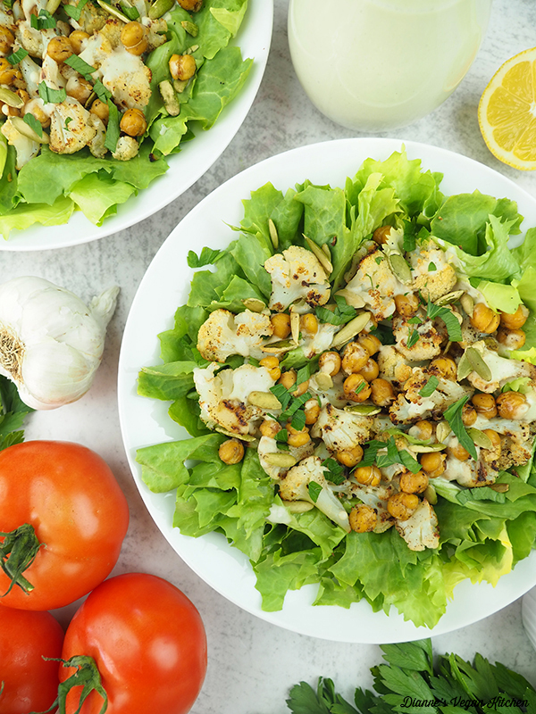 Two bowls of Roasted Cauliflower Salad with dressing, garlic, lemon, and tomatoes