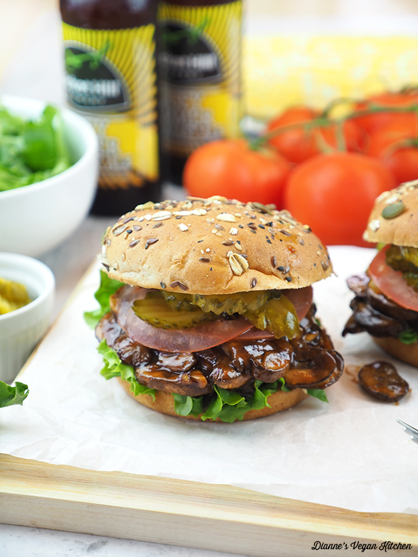 Barbecue Pulled Mushroom Sandwiches on board with tomatoes, corn, beer, and salad