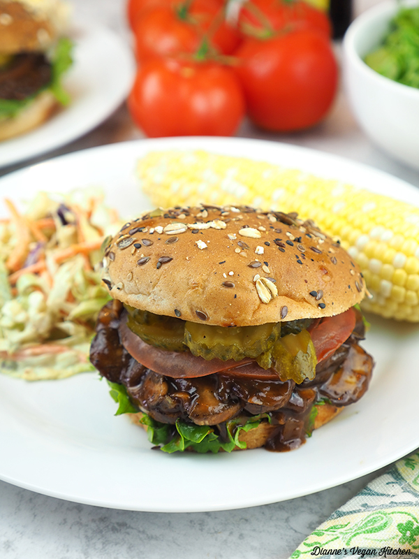 Pulled Mushroom Sandwiches with bbq sauce and pickles on plate with coleslaw and corn