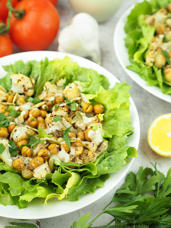 two bowls of salad with lemon, garlic, and tomatoes
