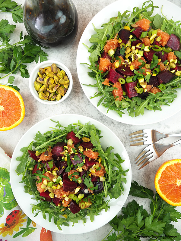two bowls of Roasted Beet Salad with oranges, dressing, and pistachios