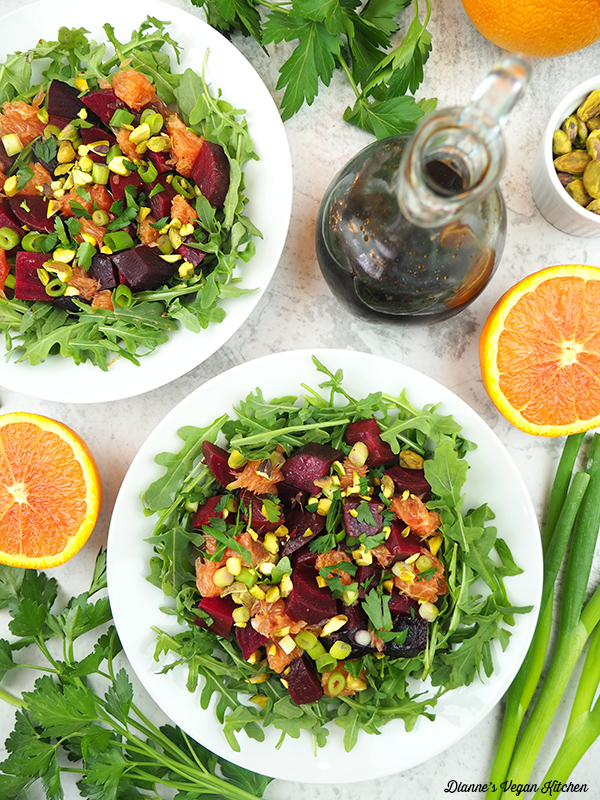 two beet salads overhead, with dressings oranges, and scallions