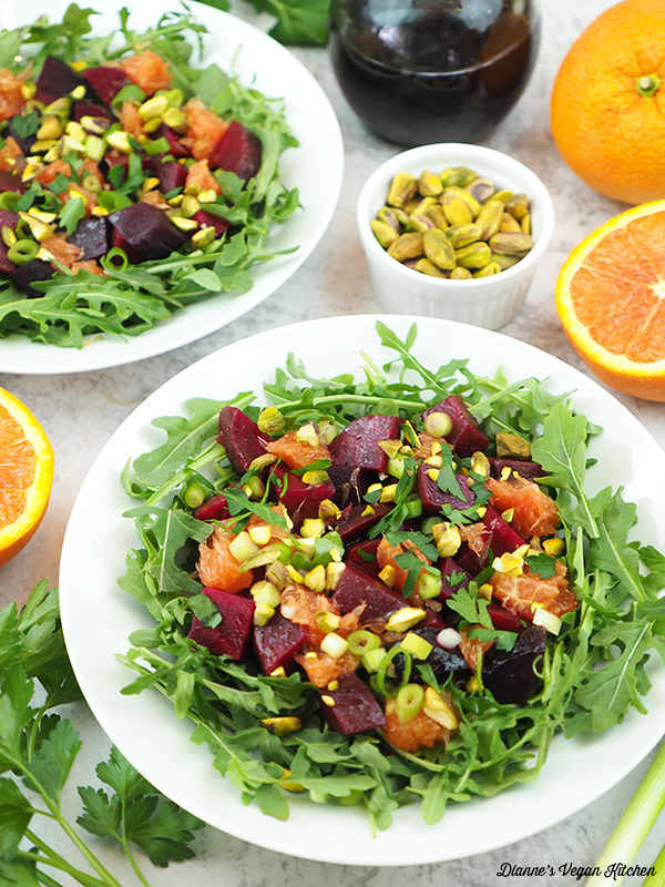 two beet salads with dressing, oranges, and pistachios