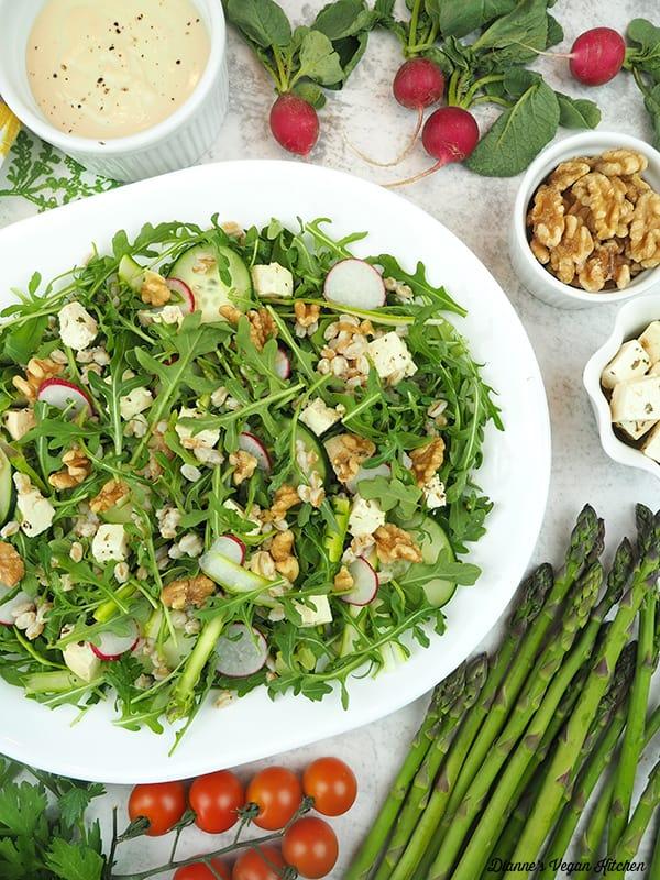 salad platter with walnuts, feta, asparagus, tomatoes, radishes, and tahini dressing