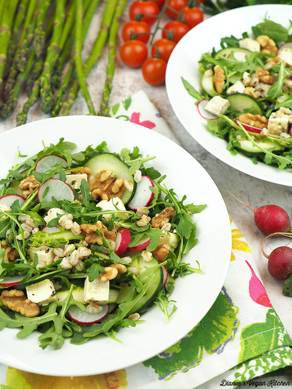 two bowls of salad with asparagus, tomatoes, and radishes