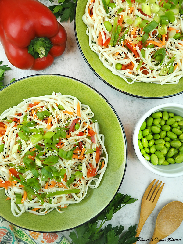 two bowls of sesame noodles with edamame, peppers and scallions