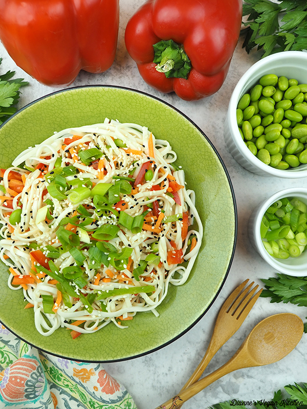 bowl of noodles with edamame, peppers and scallions