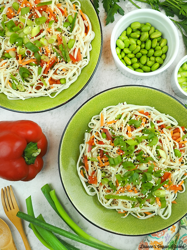 two bowls of noodles with edamame