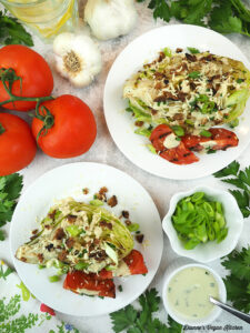 two wedge salads overhead with tomatoes, garlic, scallions, and dressing