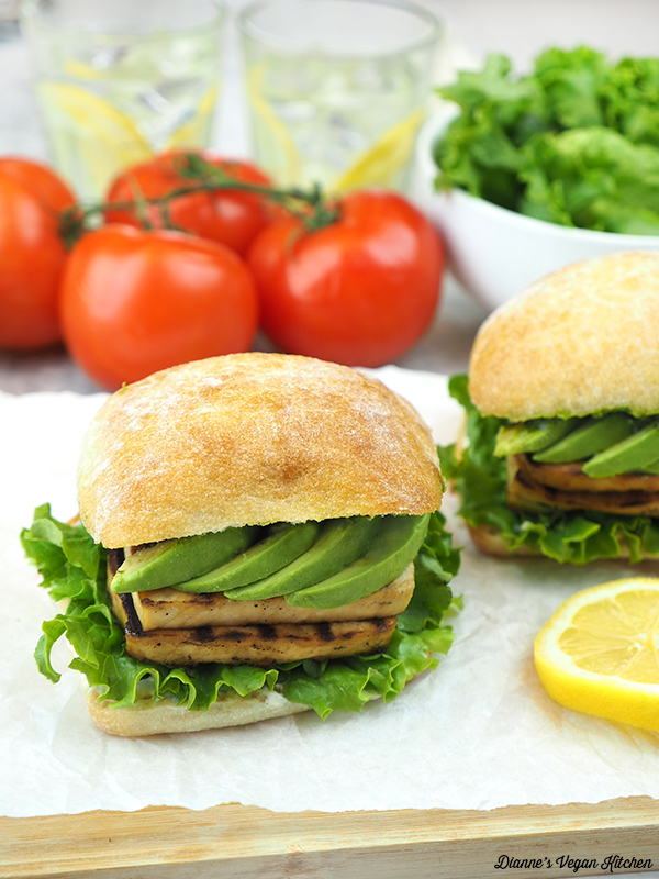 two grilled tofu sandwiches with tomatoes and salad