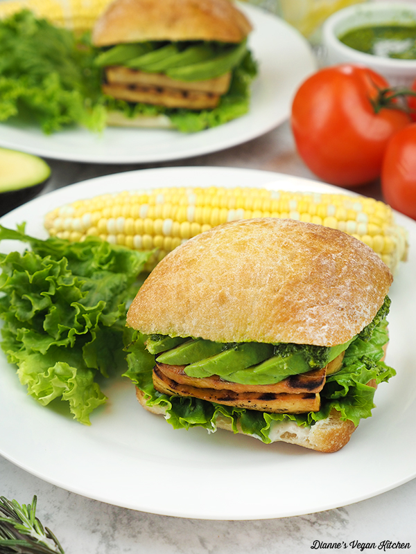 sandwiches on plates with corn and salad