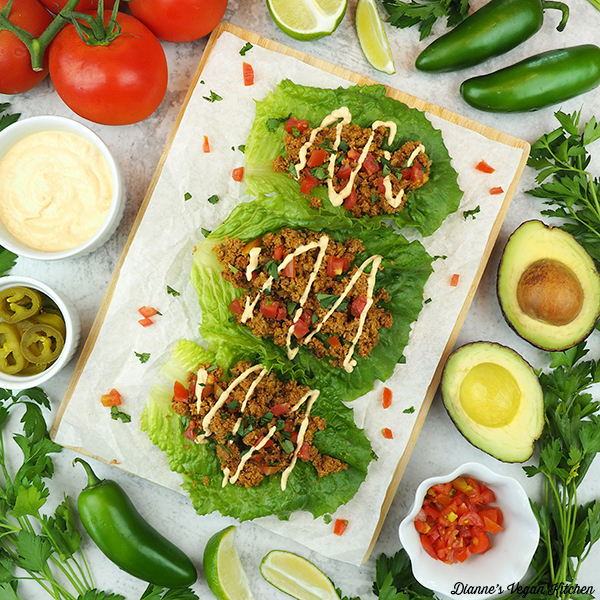 raw vegan tacos with tomatoes, jalapeños, cilantro, limes, avocado, and cheese sauce square