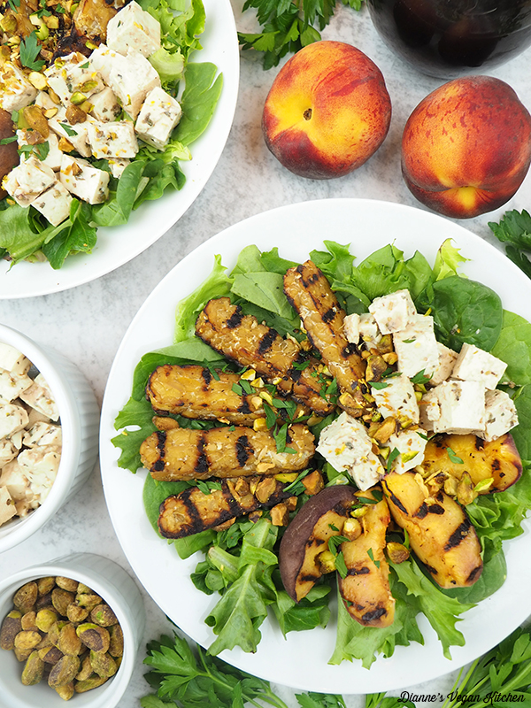 two bowls of salad with peaches, pistachios, and tofu feta