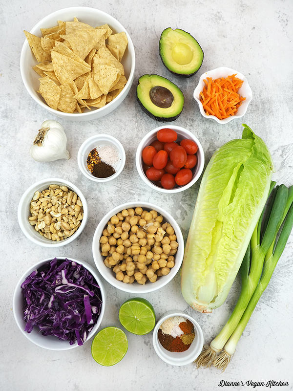 tortilla chips, avocado, tomatoes, carrots, lettuce, scallions, spices, chickpeas, limes, cabbage, and garlic