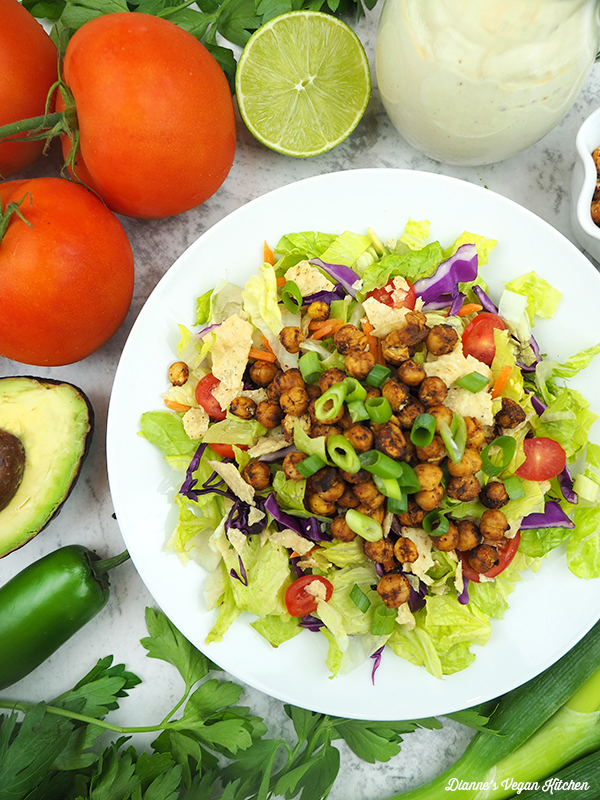 bowl of taco salad with tomatoes, lime, avocado, and chili