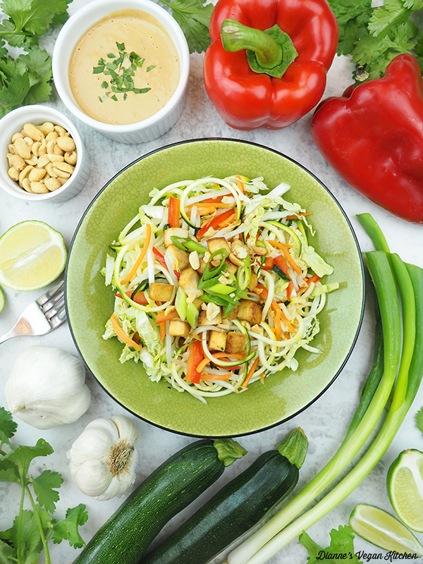 one bowl of zucchini noodles surrounded by peppers, scallions, zucchini, limes, garlic, cilantro, peanuts, and peanut sauce