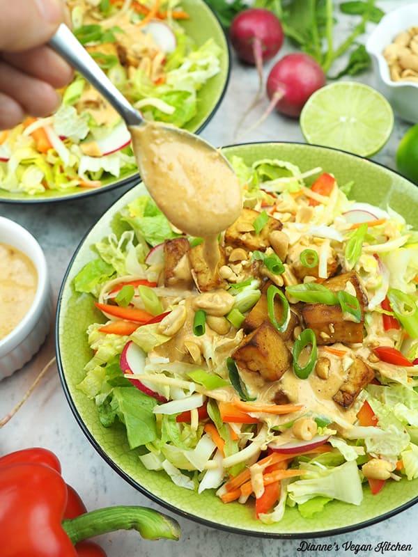 spooning dressing onto salad