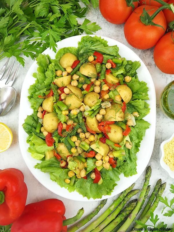 platter of escarole salad with tomatoes, dressing, parmesan, asparagus, red peppers, and lemon