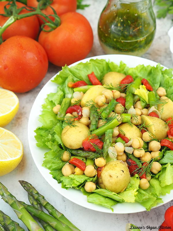 platter of escarole salad with tomatoes, dressing, lemons, and asparagus