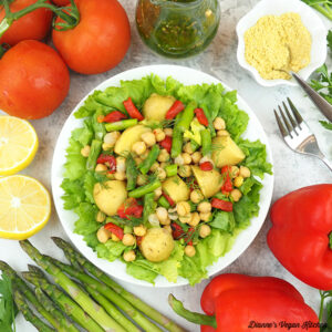 platter of escarole salad with tomatoes, dressing, lemons, parmesan and asparagus
