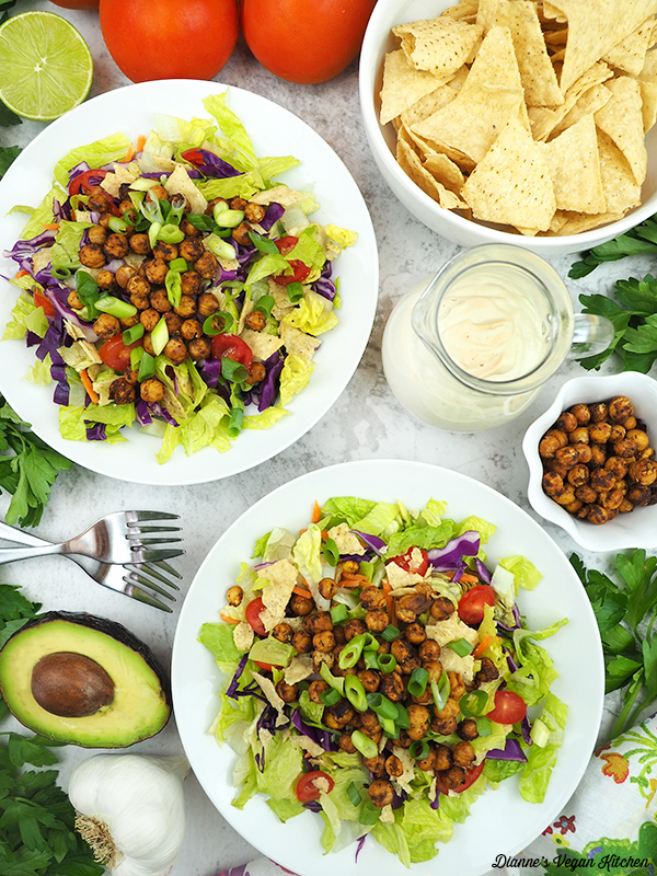 two bowls of chickpea taco salad with chips, dressing, chickpea, and avocado