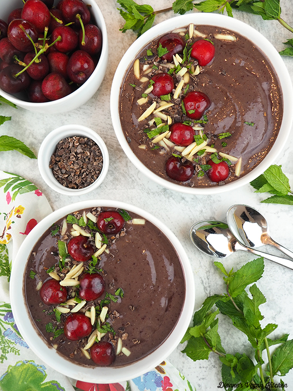 two smoothie bowls with cherries and cacao nibs