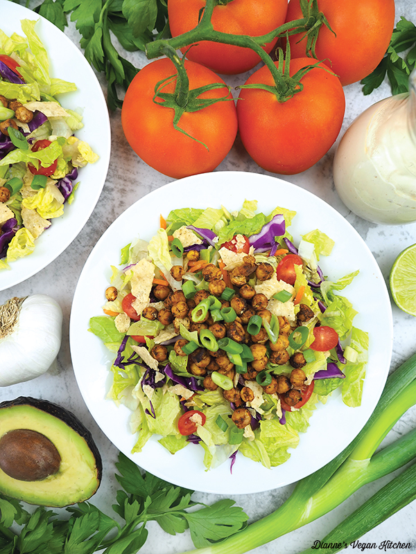 chickpea taco salad with tomatoes, dressing, garlic, and avocado