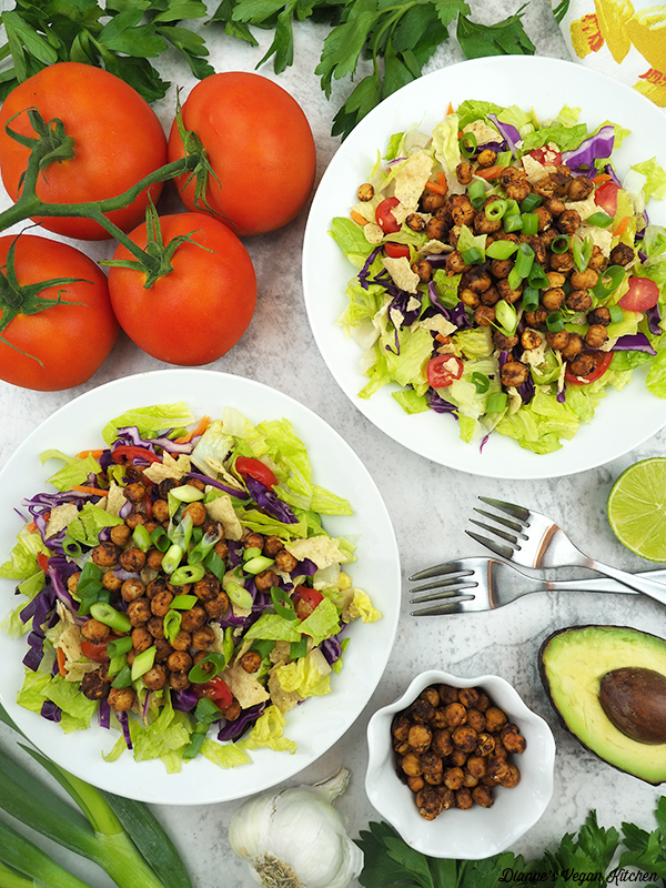 two bowls of taco salad with tomatoes and avocado
