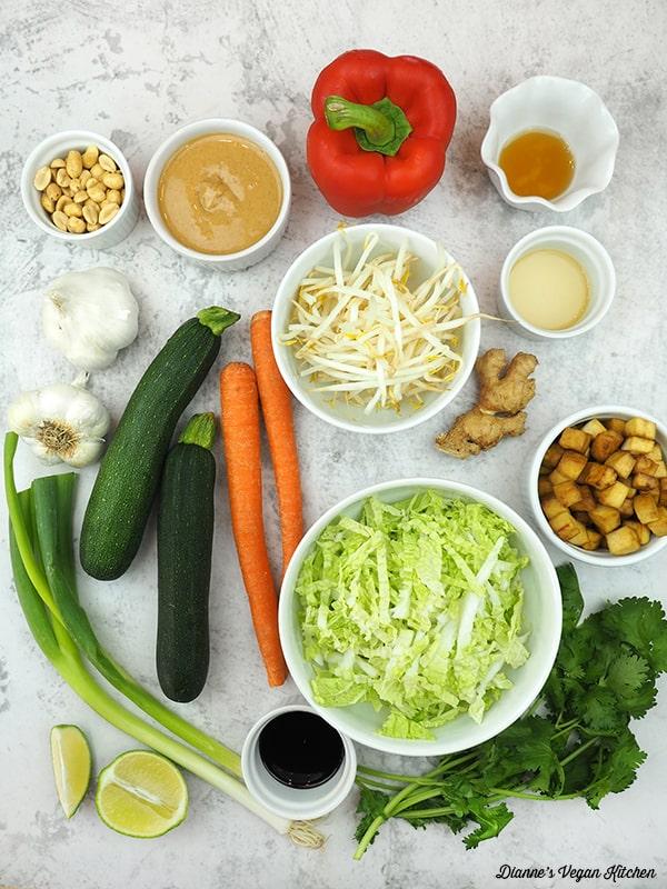 peanuts, peanut sauce, pepper, sprouts, cabbage, peanuts, carrots, zucchini, scallions, limes, garlic, and cilantro