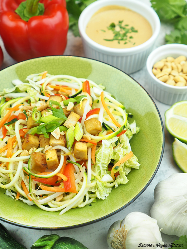 close up of zucchini noodles with peppers, peanut sauce, peanuts, limes, and garlic