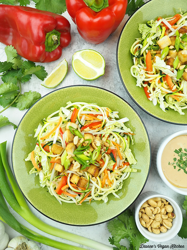 two bowls of Peanutty Pad Thai Zoodles with limes, peppers, peanut sauce, peanuts, scallions, and cilantro