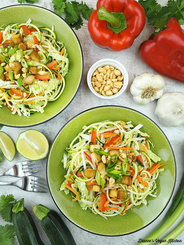 two bowls of zoodles with peanuts, limes, garlic, peppers, and forks