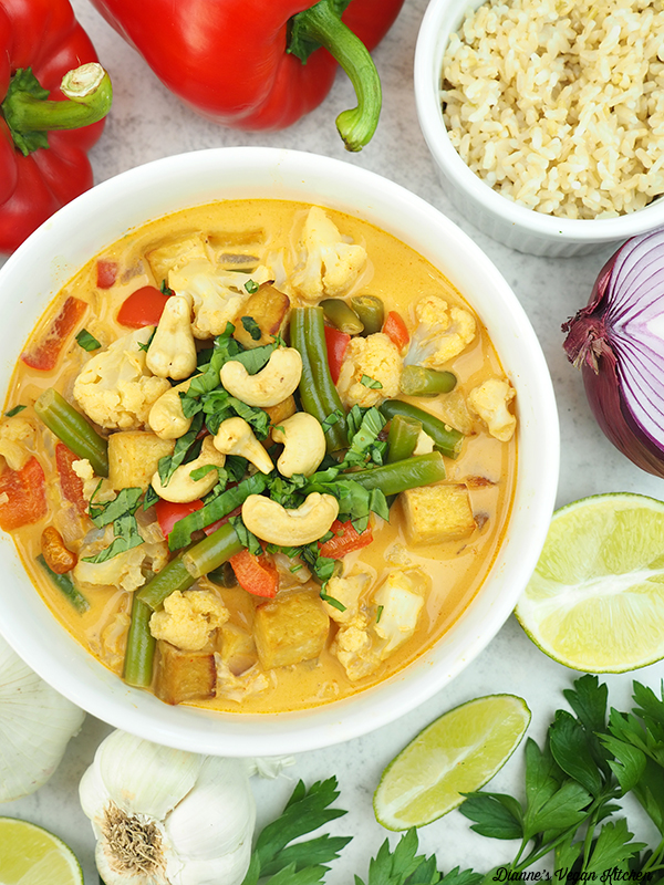 one bowl of slow cooker vegetable curry overheard with rice, onion, lime, peppers, and garlic